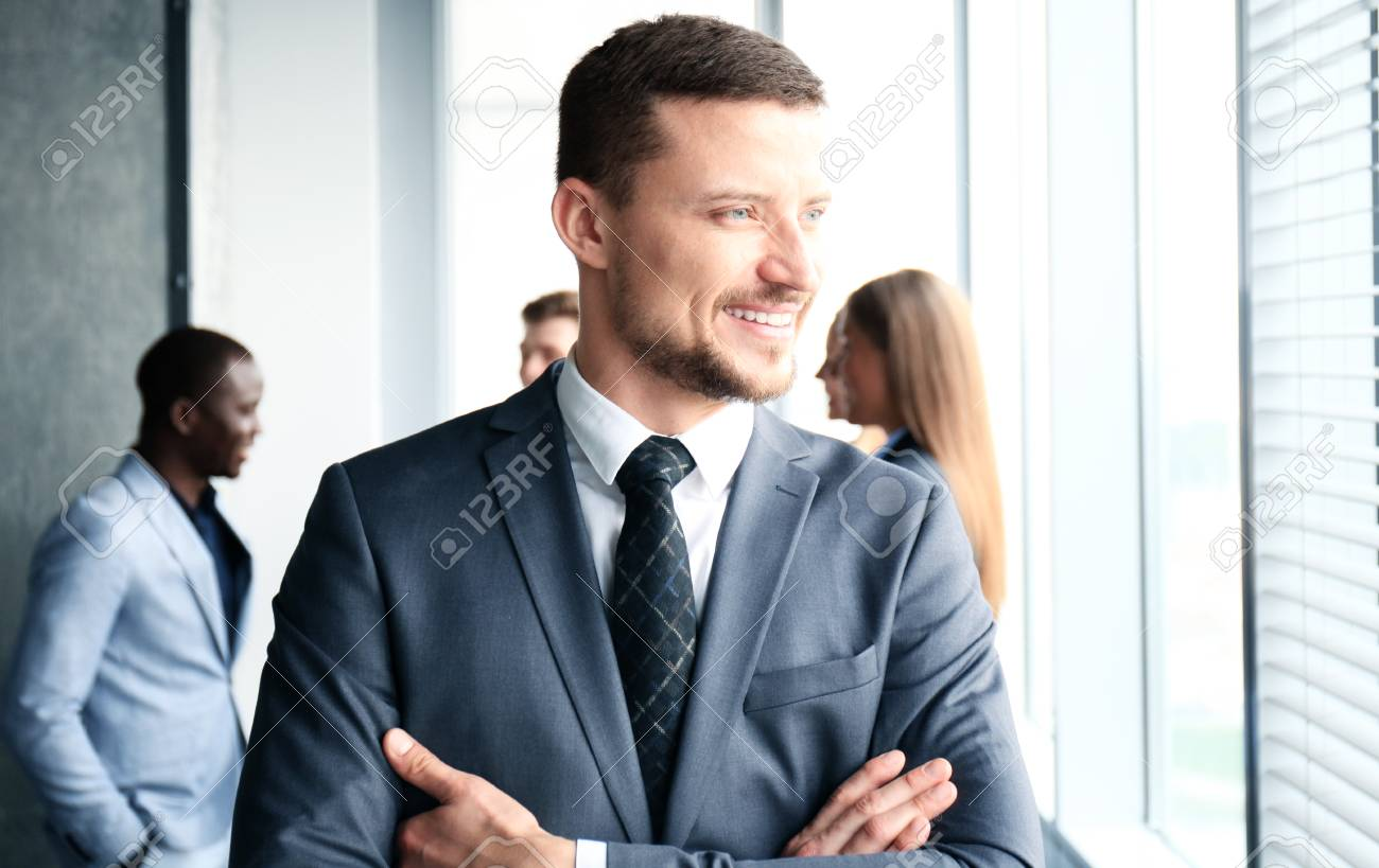 Businessman with colleagues in the background in office - 69561085
