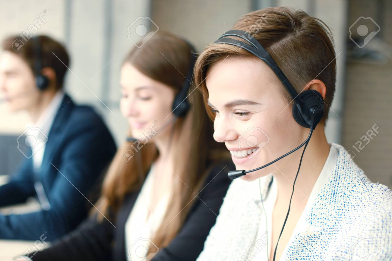 Attractive positive young businesspeople and colleagues in a call center office. - 82333603