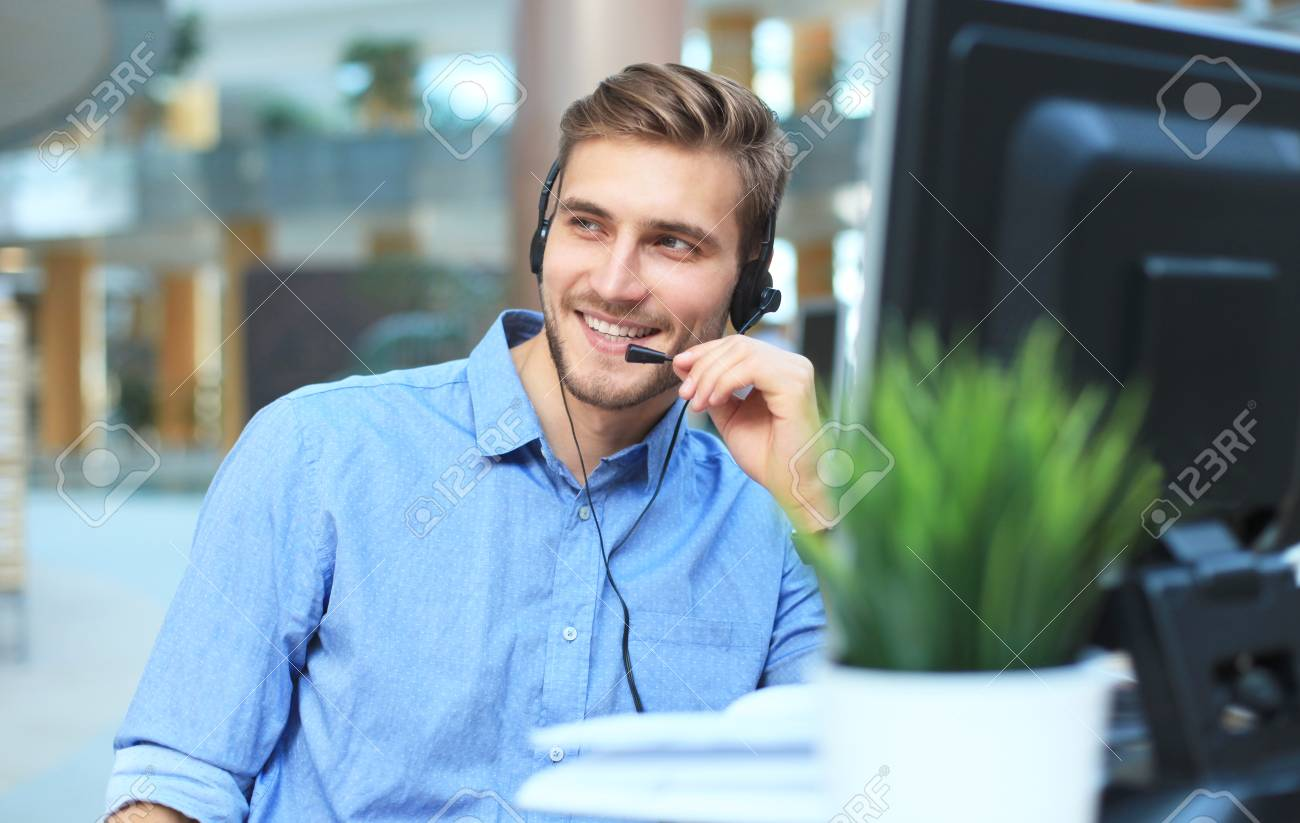 Smiling friendly handsome young male call centre operator. - 103921081