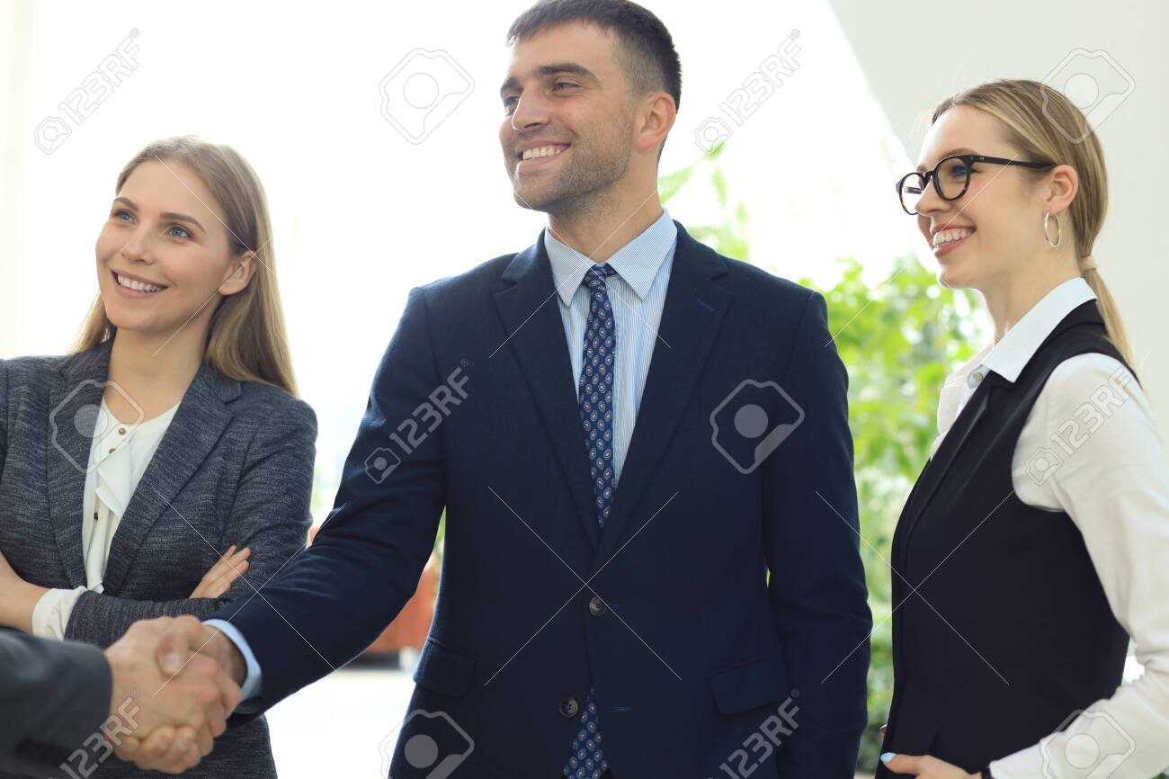 Business people shaking hands, finishing up a meeting - 122474507