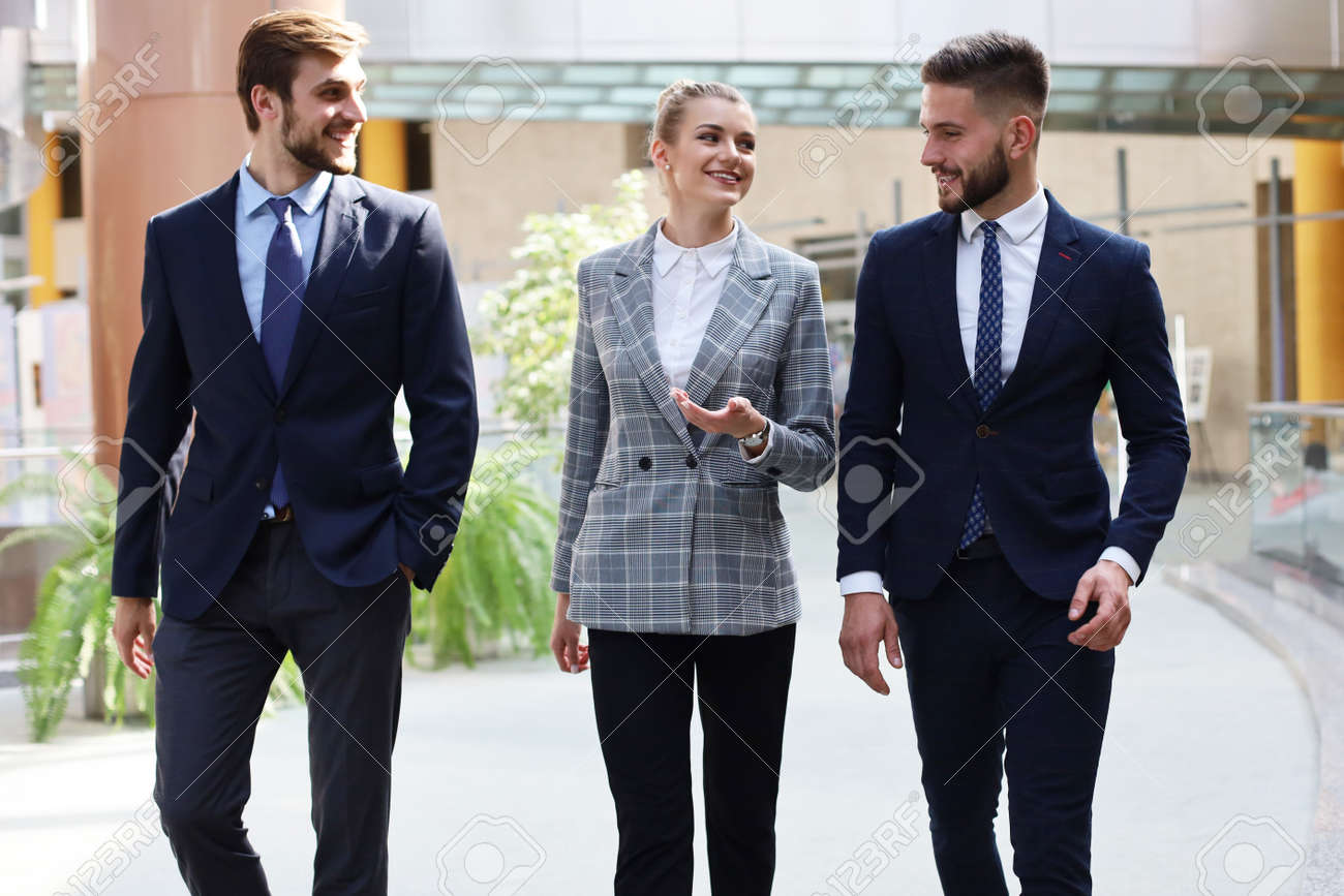 businesspeople group walking at modern bright office interior - 125655080