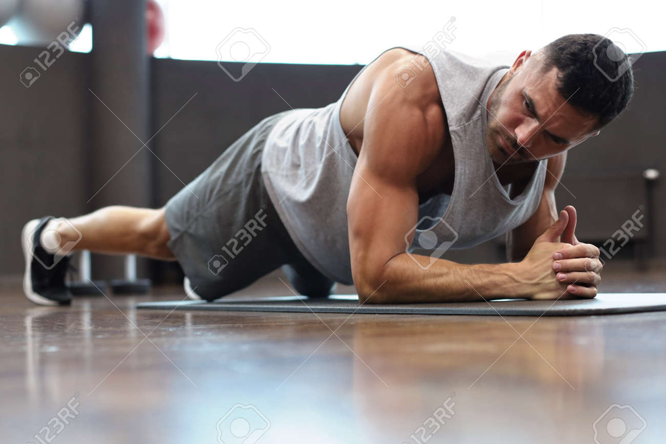 Portrait of a fitness man doing planking exercise in gym - 126908621