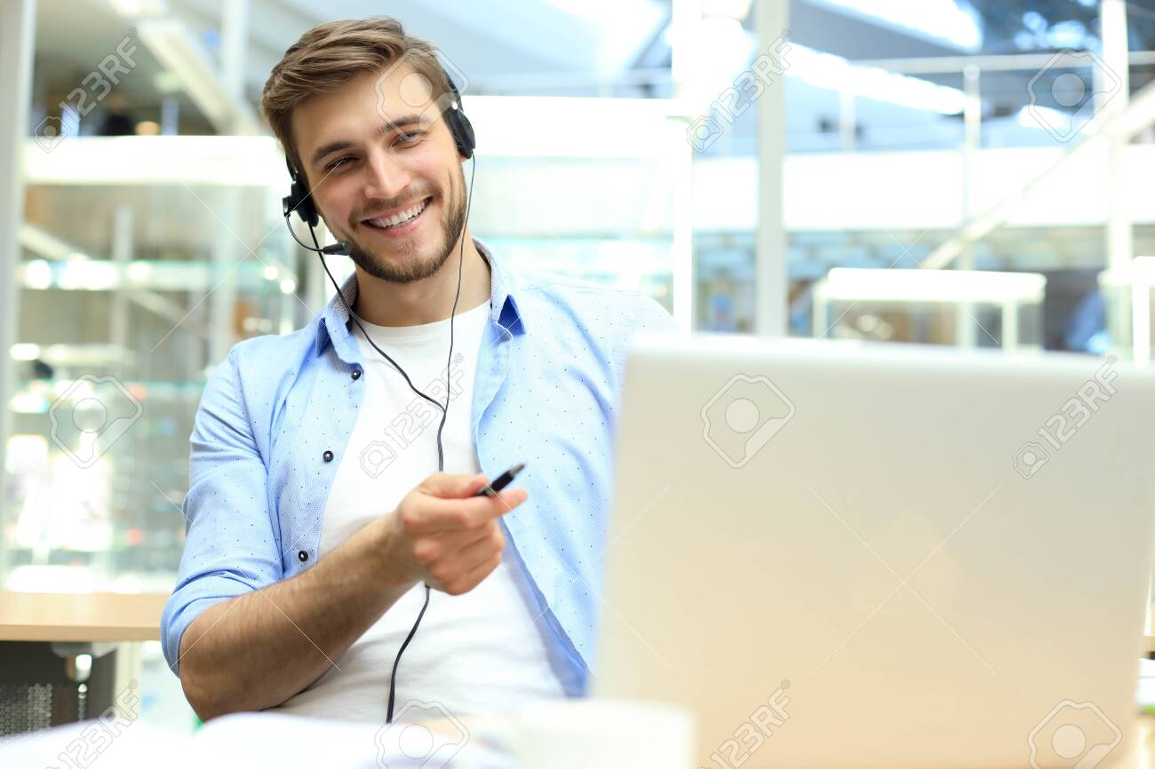 Smiling friendly handsome young male call centre operator - 128247598