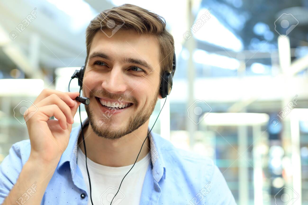 Smiling friendly handsome young male call centre operator - 128247594