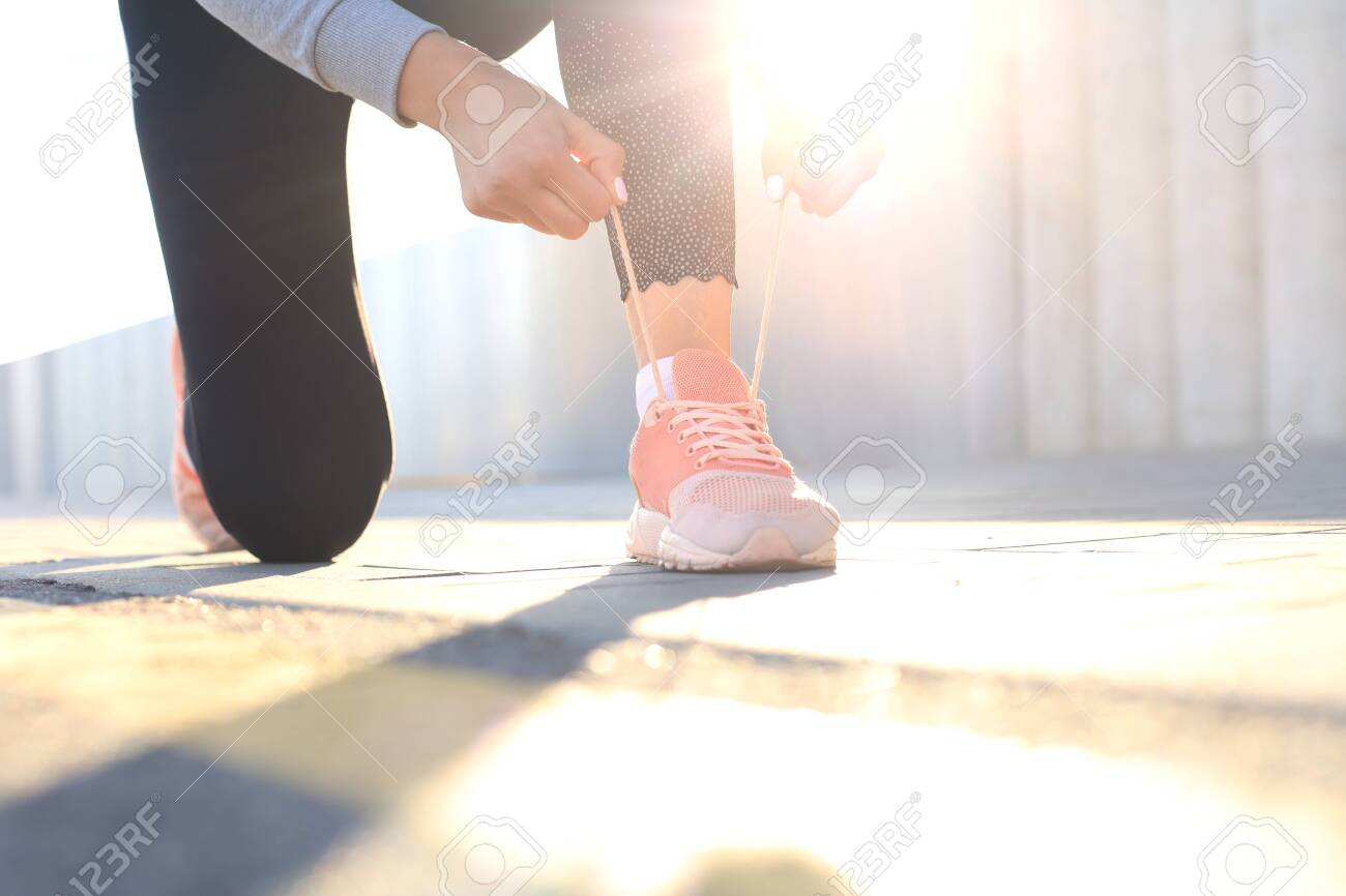 Closeup of unrecognizable sport woman tying sports shoes during evening run outdoors - 130350229