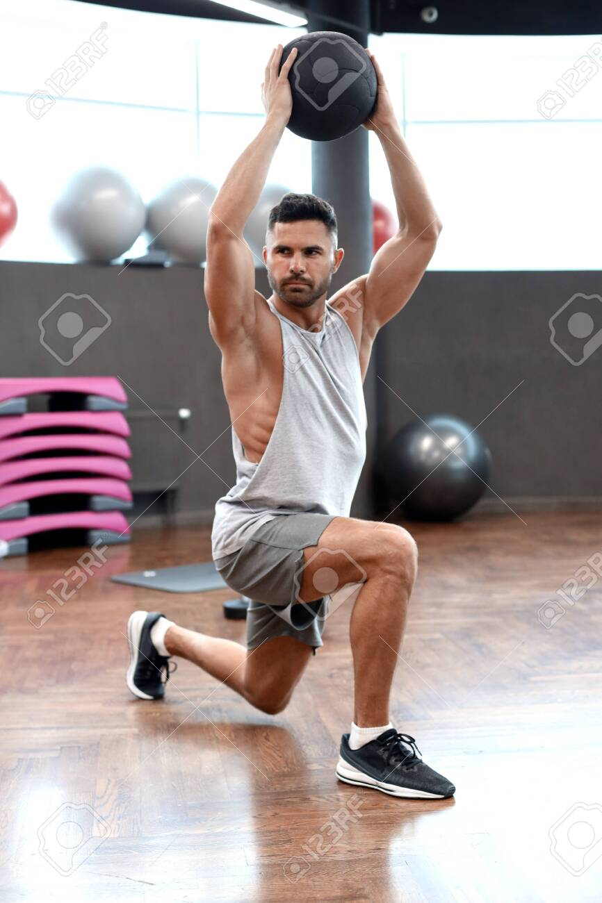 Fit and muscular man exercising with medicine ball at gym. - 130734626