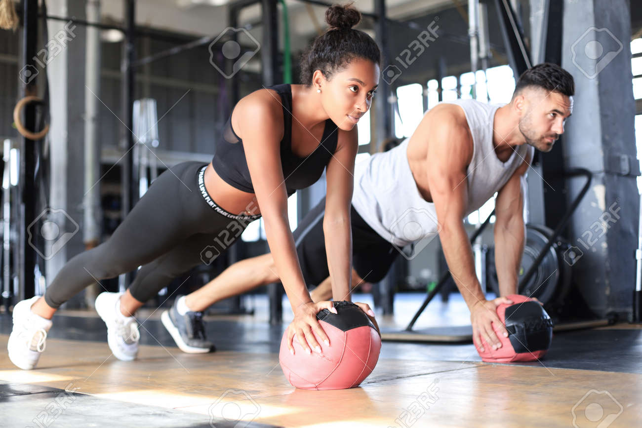 Beautiful young sports couple is working out with medicine ball in gym - 134087978