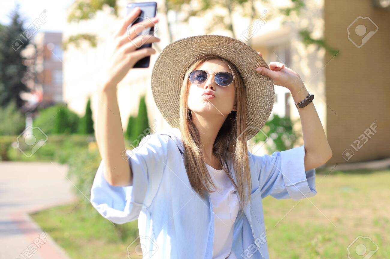Beautiful young blonde girl using mobile phone while standing outdoors - 135116101