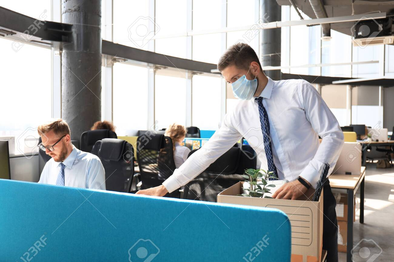 Dismissal employee in an epidemic coronavirus covid-19. Sad dismissed worker are taking his office supplies with him from office - 143334478