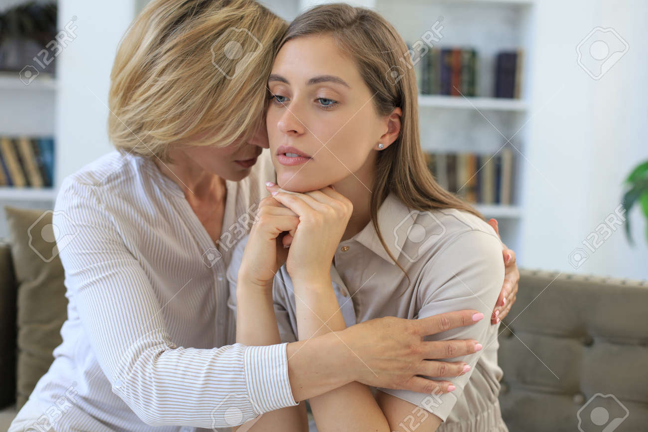 Concerned middle aged mother and adult daughter sit on couch having serious conversation, listen to her sharing problems. - 154086732
