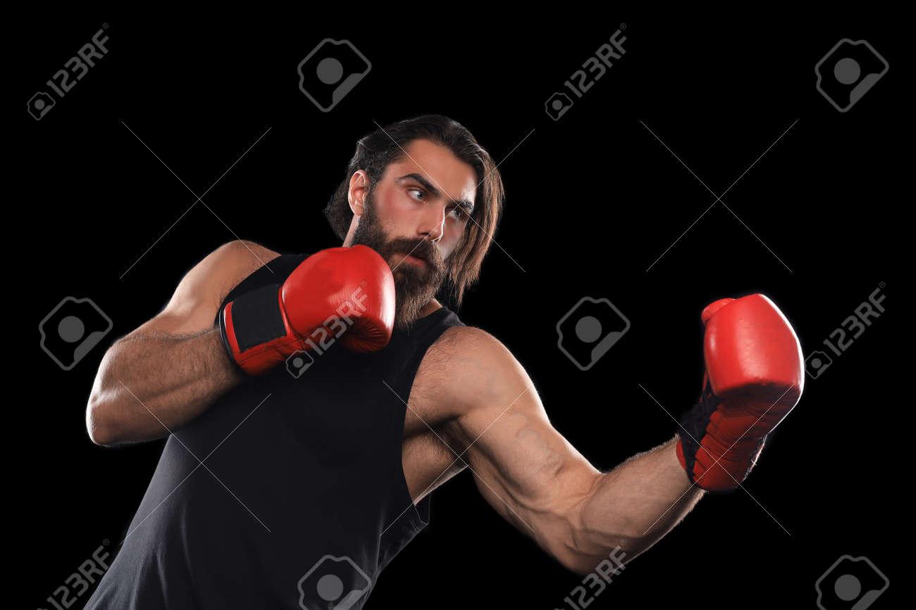 Kickboxer man fighting against black background. Sport concept - 157331421