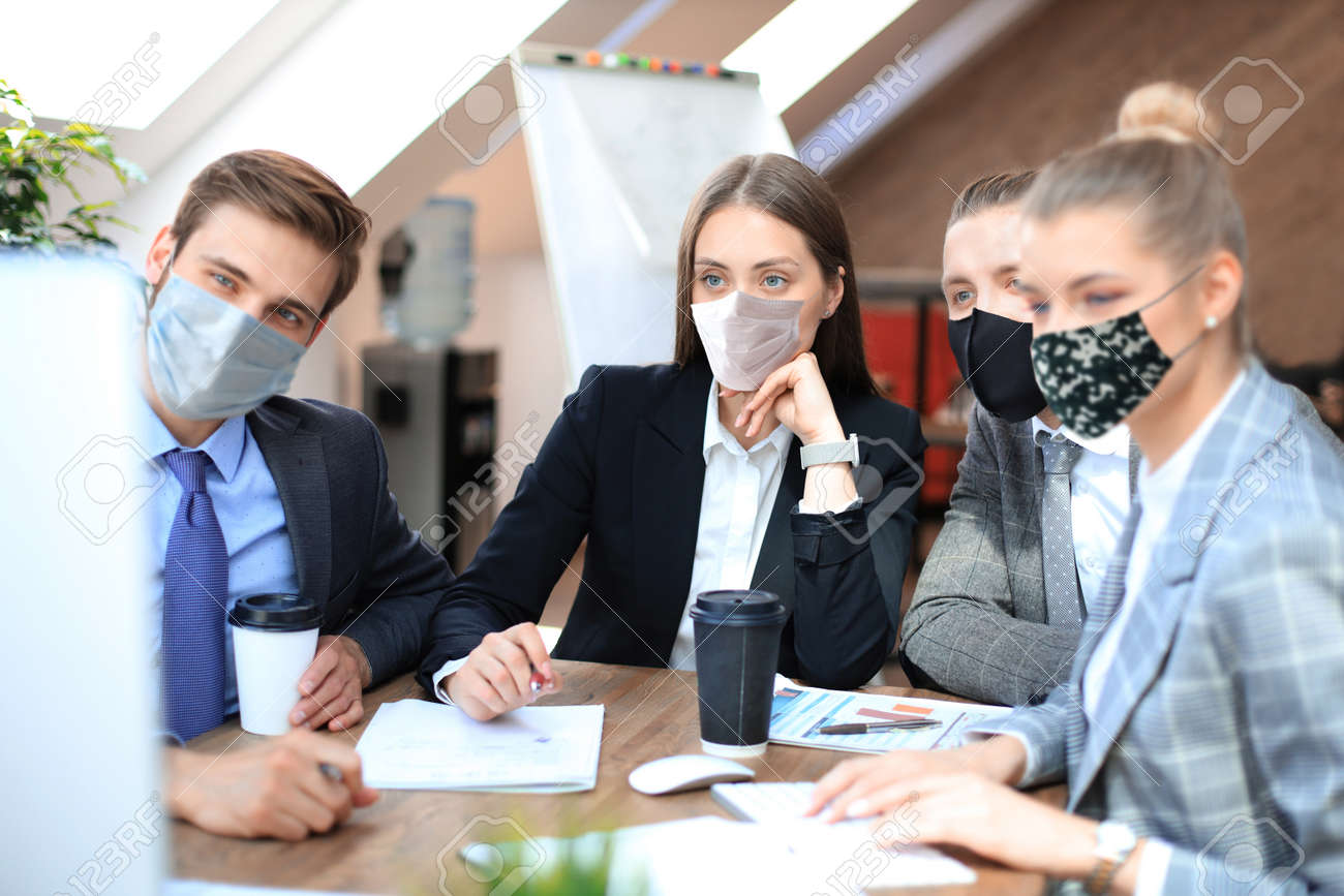 Group of young business people working, communicating while sitting at the office desk together with colleagues in preventive masks during epidemy. - 159029655