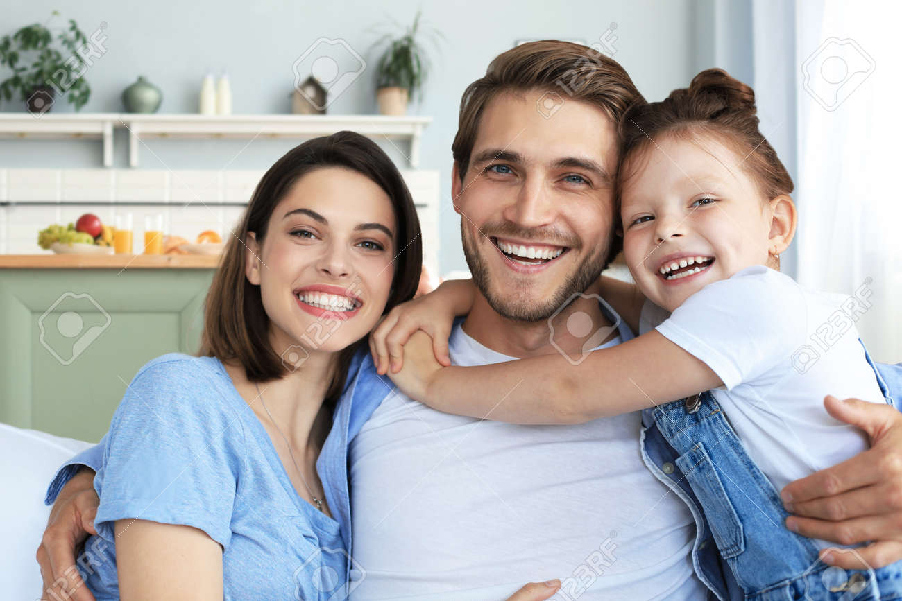 Positive friendly young parents with smiling little daughter sitting on sofa together while relaxing at home on weekend - 165748423