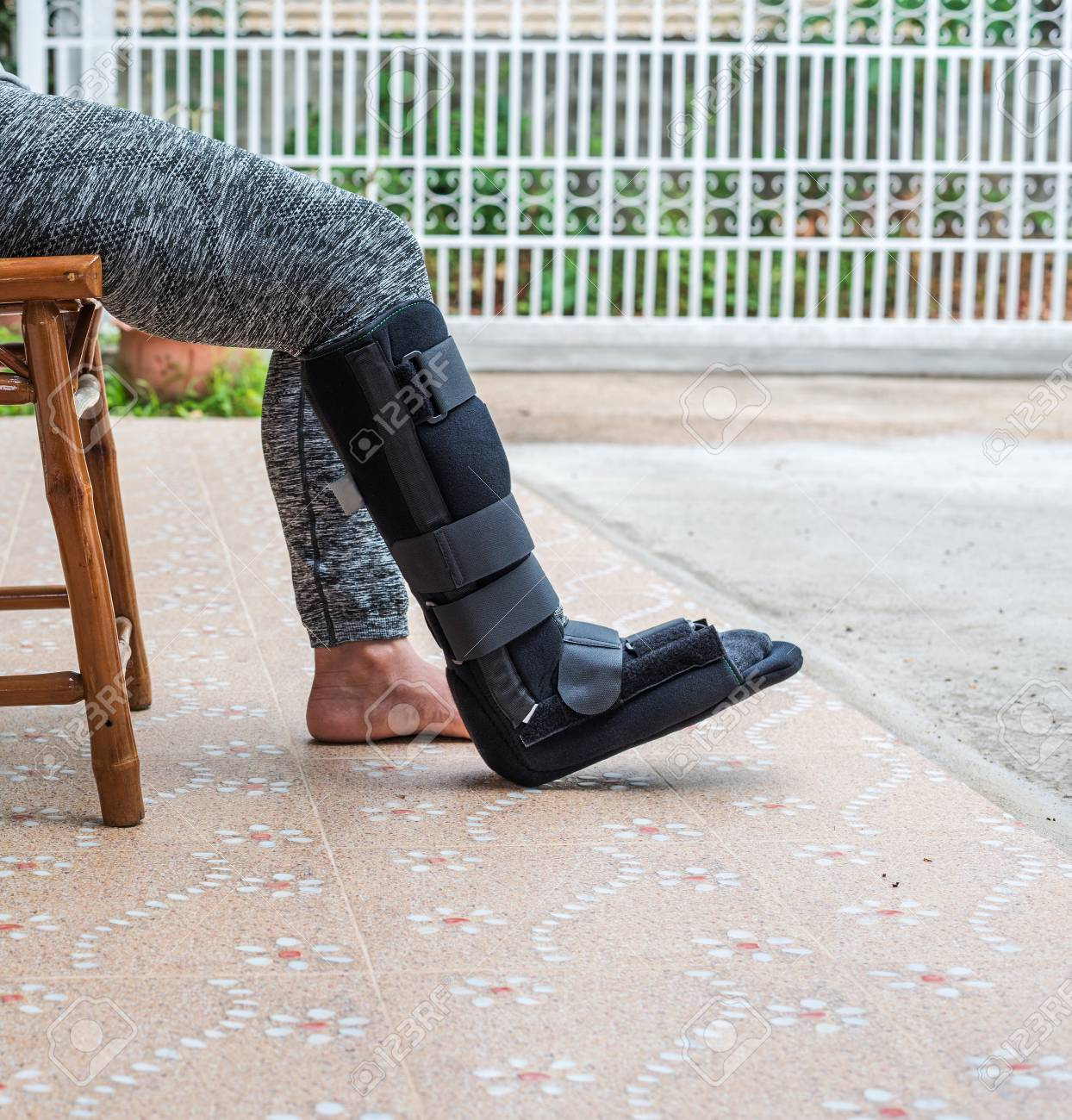 Woman With Black Cast On Leg Sitting On Wood Chair Body Injury