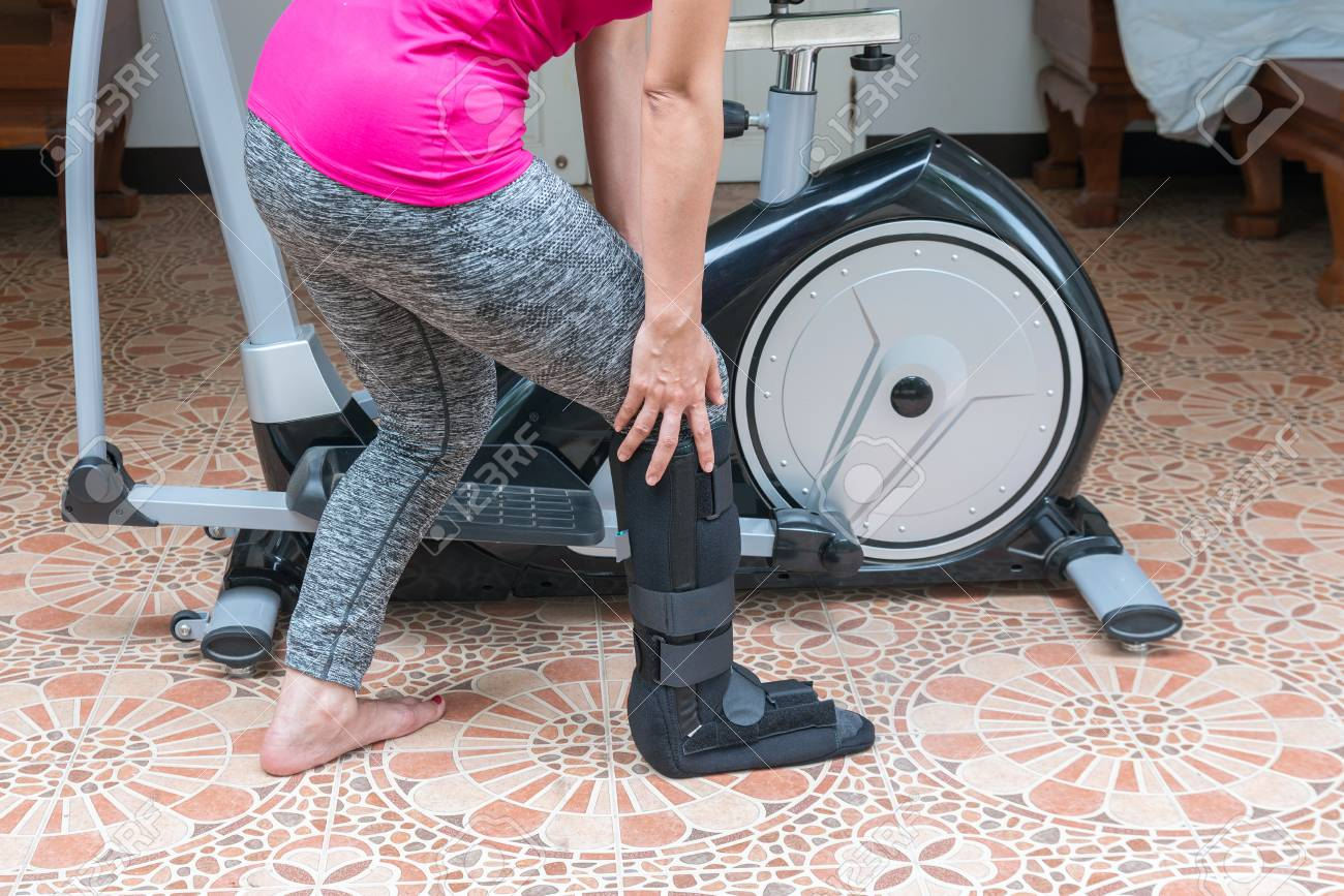 Woman holding painful leg in pain with the exercise bike at home