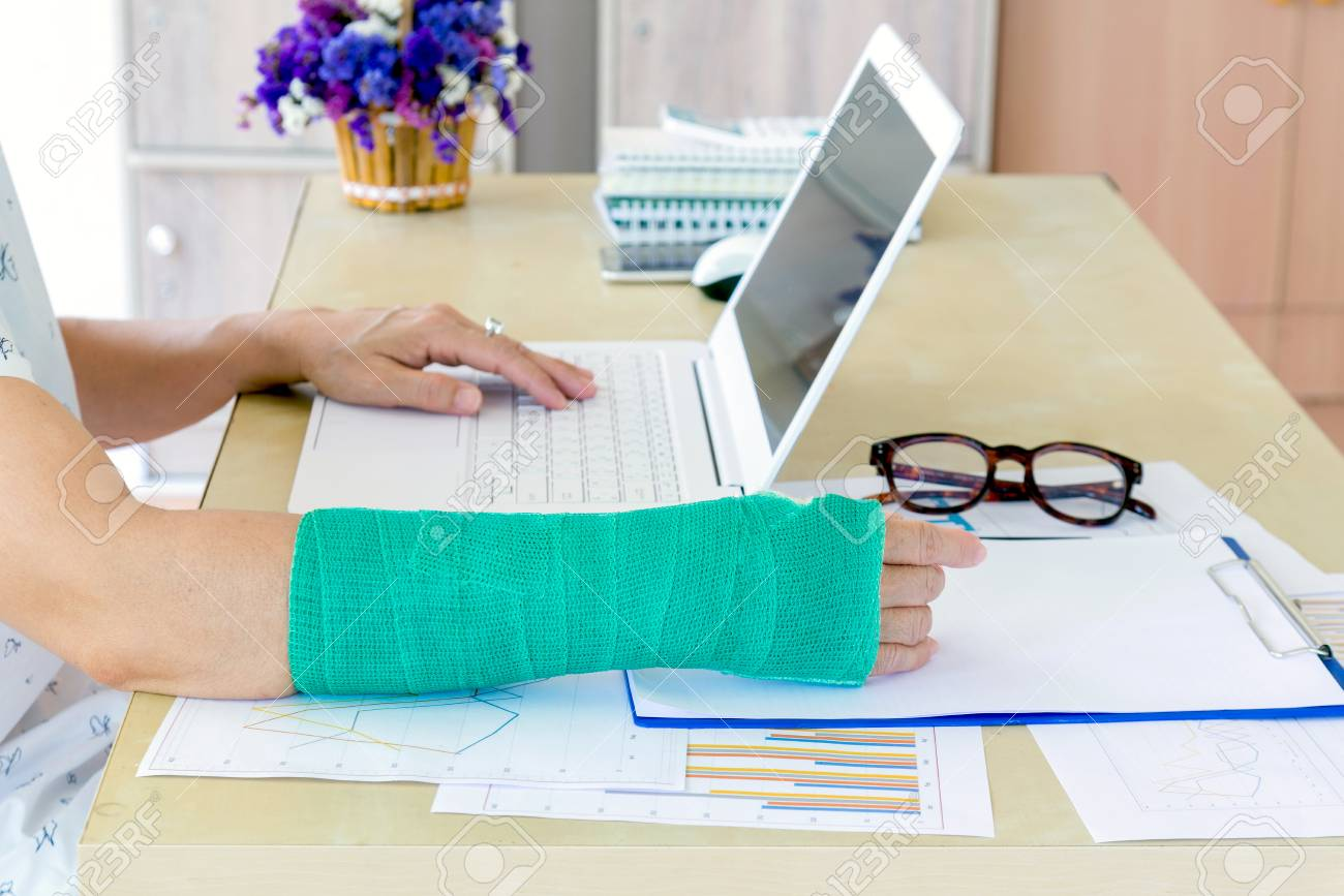 Working Woman With Green Cast On Arm Working On Laptop In Office