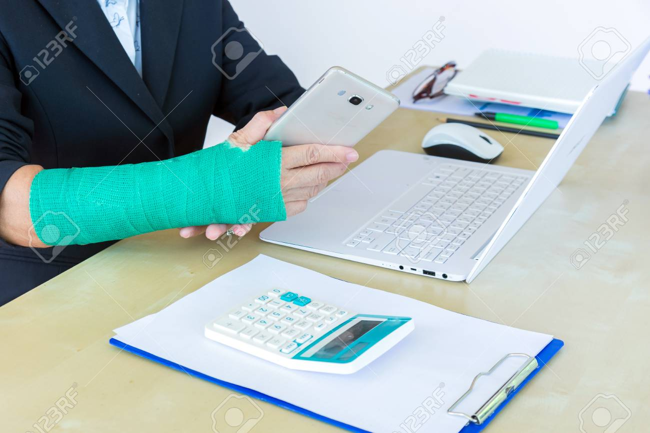 Business Woman With Green Cast On Arm Holding Smart Phone And