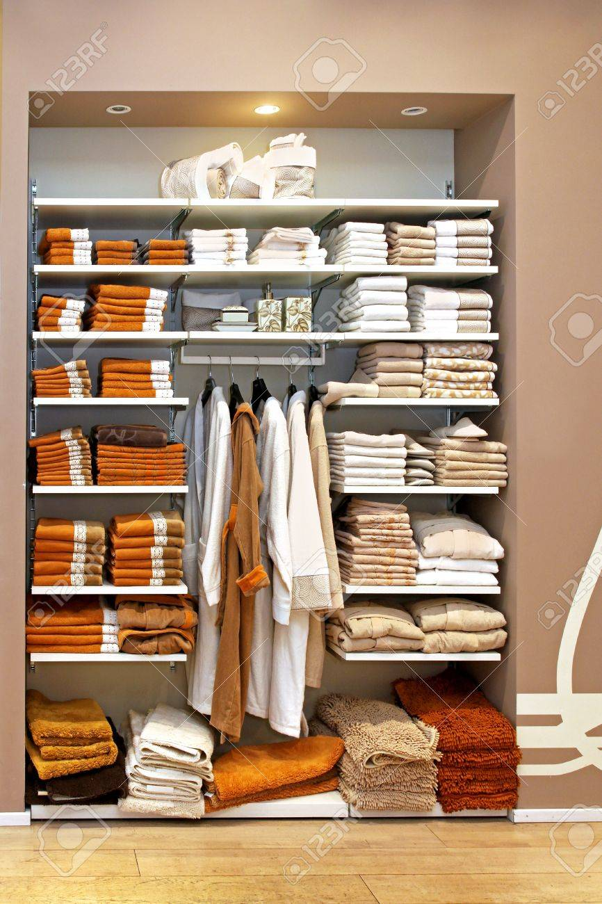 Big Storage Space With Towels On Shelf And Bathrobes On Hangers Stock Photo    12662178