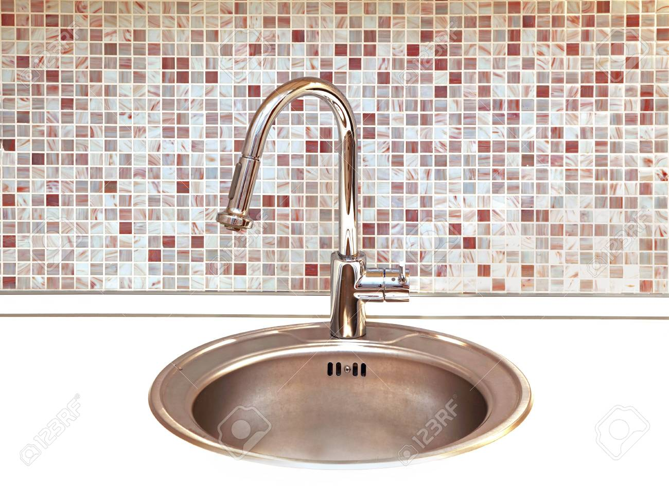 Modern kitchen faucet with mosaic tiles in background