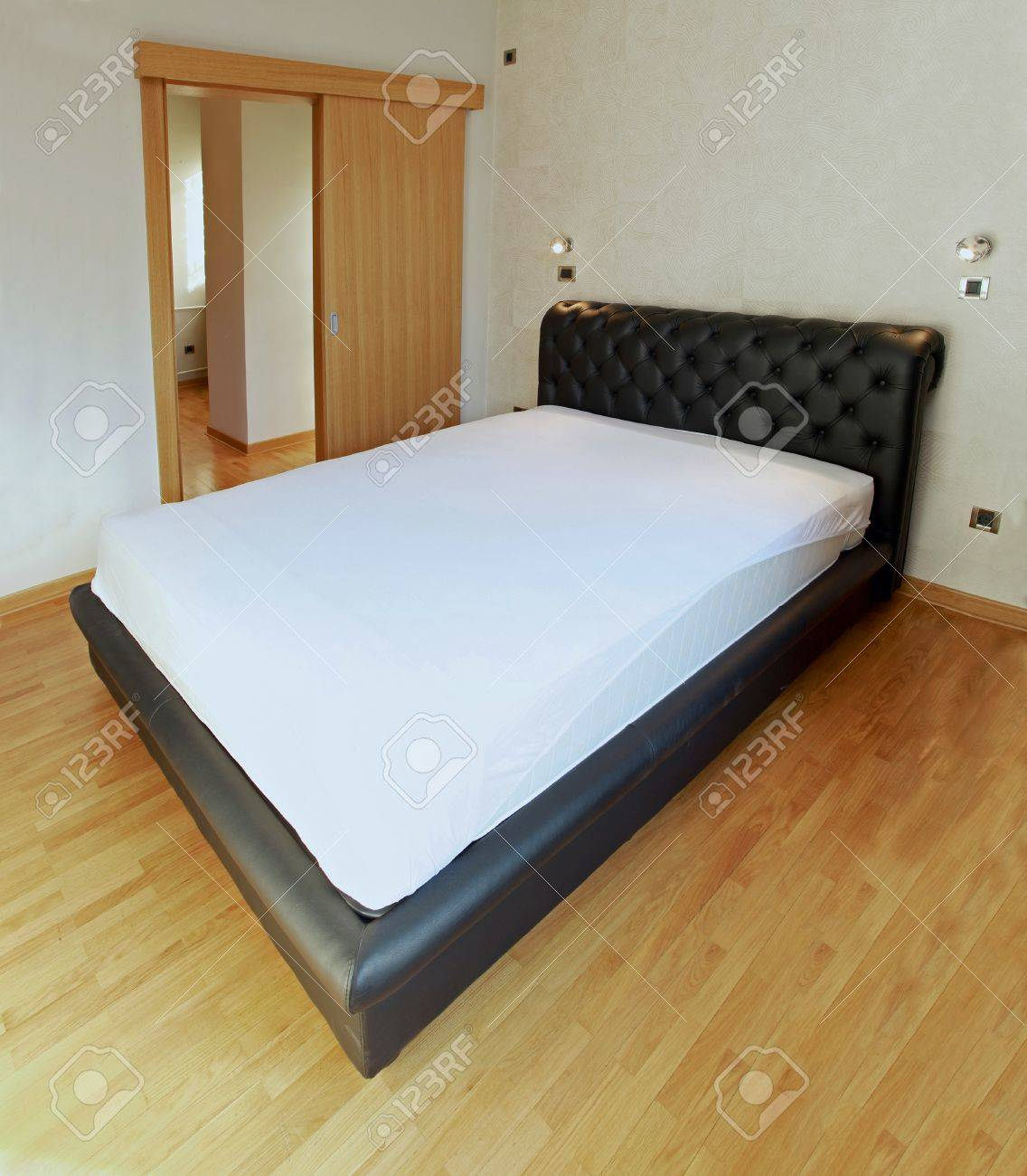 Large leather double bed in empty bedroom Stock Photo - 16684087