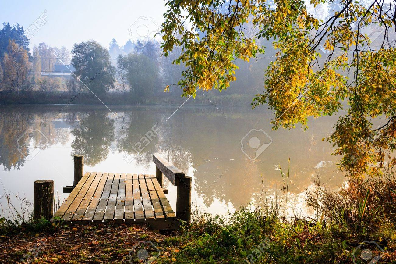 Autumn landscape with mist on the lake and a pier bathing on sunshine Stock Photo - 15482929