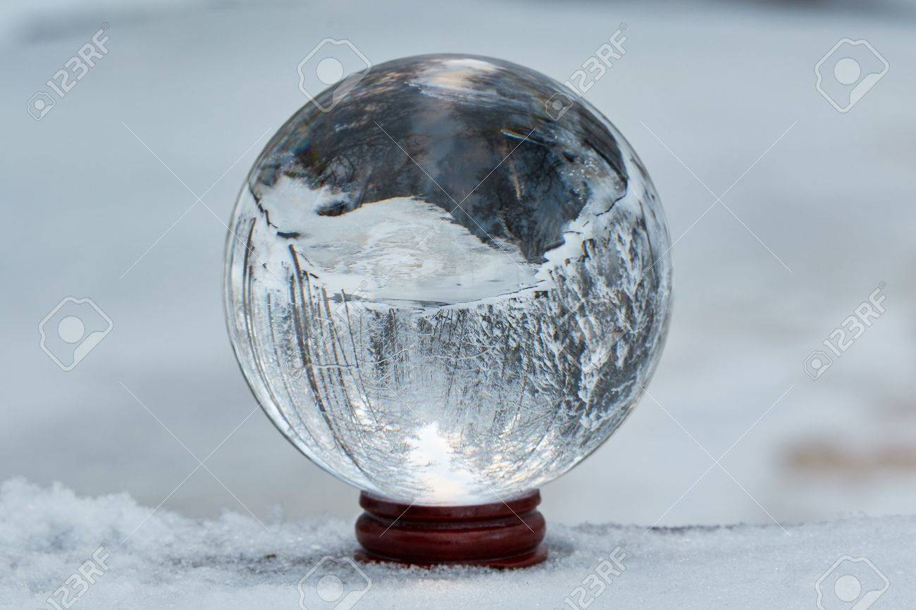 Winter scene with a transparent crystal ball reflecting the snowy landscape. Icy river appearing upside down on the ball. Stock Photo - 52046407