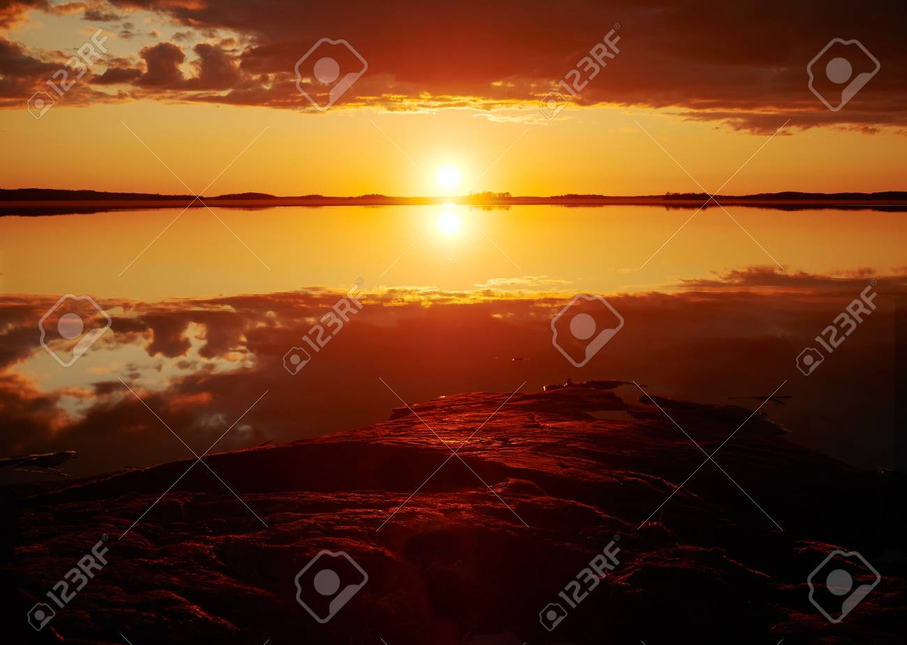 Sunset with crimson red color in the clouds and the rocks on