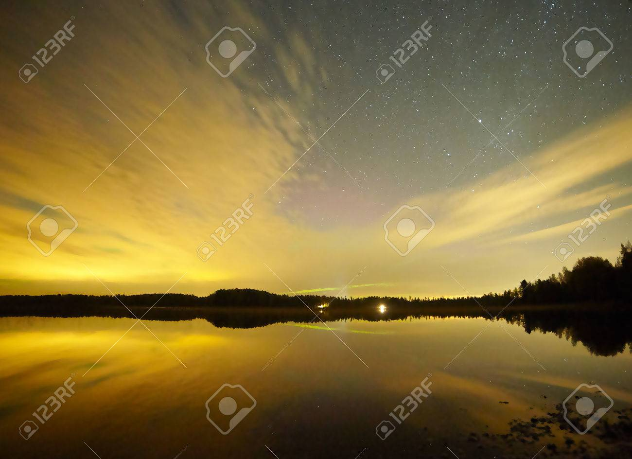 Stars and sunset in Finland. Reflection of the forest skyline in the calm water of a lake. Stock Photo - 77577466