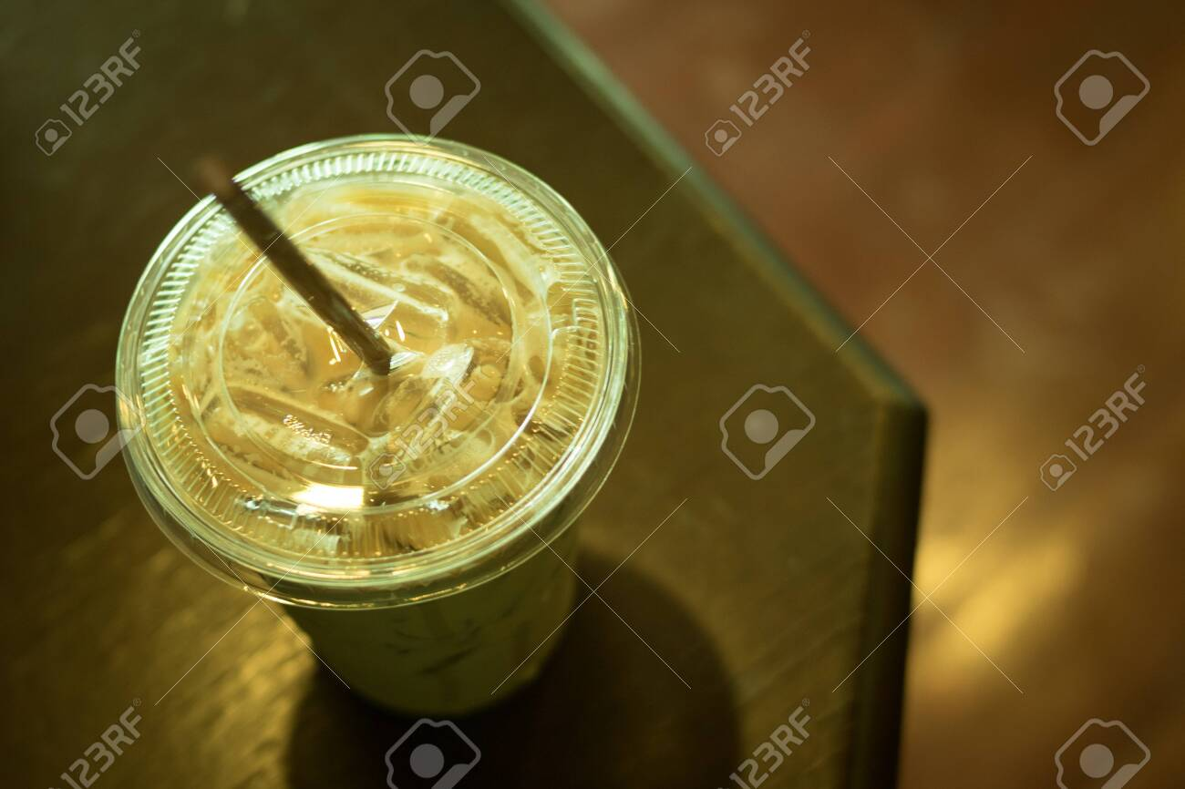 Ice coffee latte in plastic cup on top table, color vintage style, selective focus - 121044728