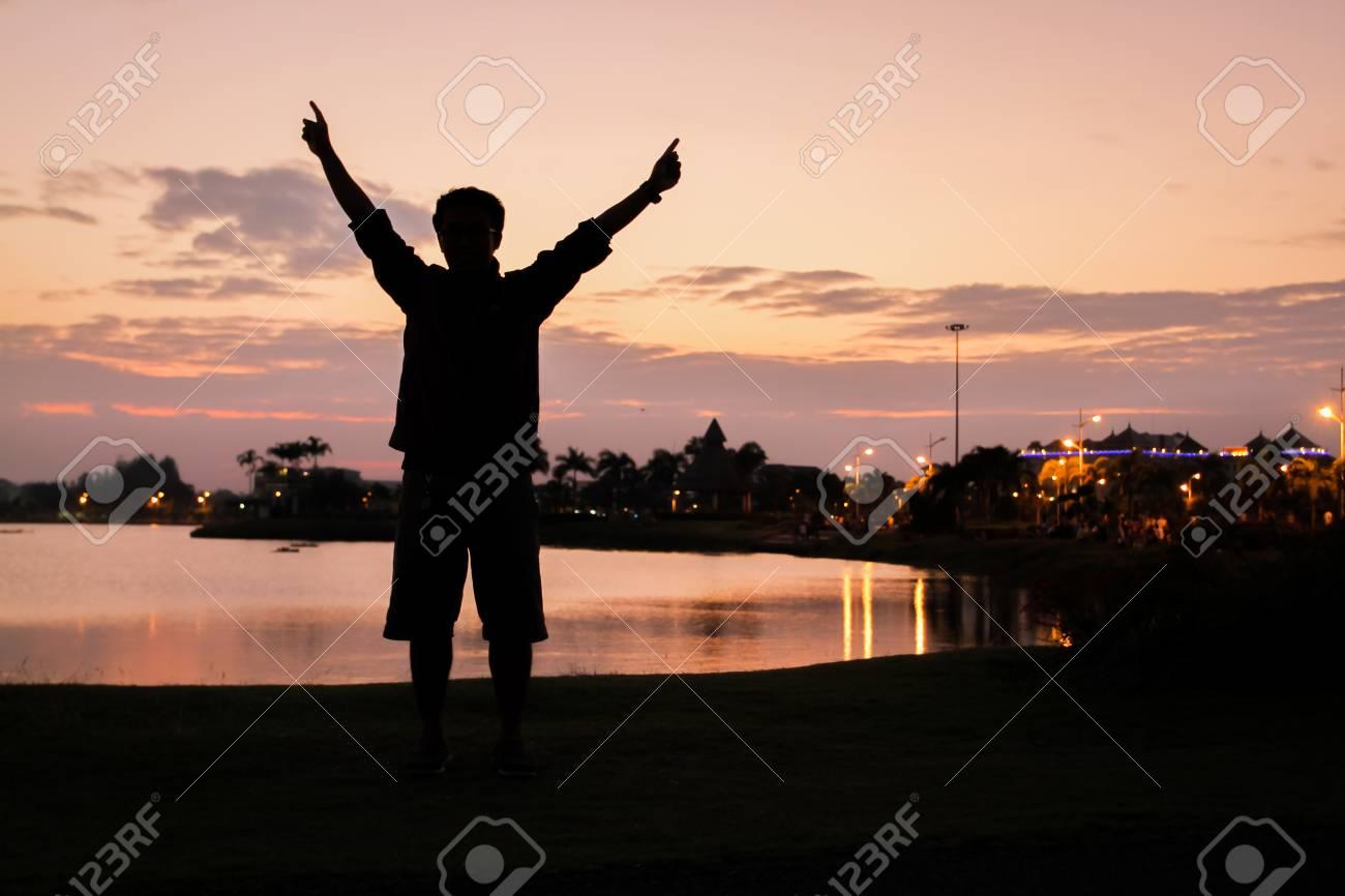 aaef60a28a Foto de archivo - Silueta de un hombre feliz brazos recaudación exitosa  hacia el cielo en la puesta de sol de iluminación