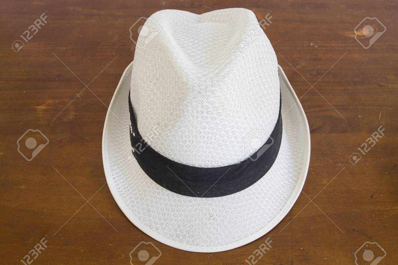 Stock Photo - White hat with a hatband on a wooden table against dark  background d7f99e57d49e