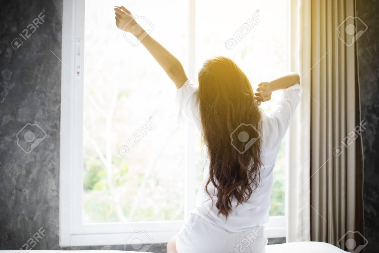 Asian woman Beautiful young smiling woman sitting on bed and stretching in the morning at bedroom after waking up in her bed fully rested and open the curtains in the morning to get fresh air. - 98483181