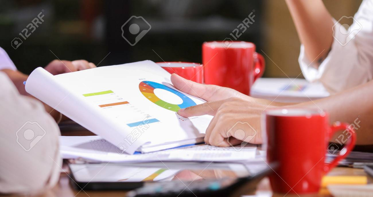 Asian businesswomen analysis documents on office table with laptop computer and graph financial diagram working in the background - 122588391