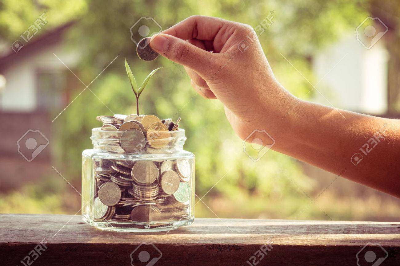 hand putting money coins  with filter effect retro vintage style Stock Photo - 39964931
