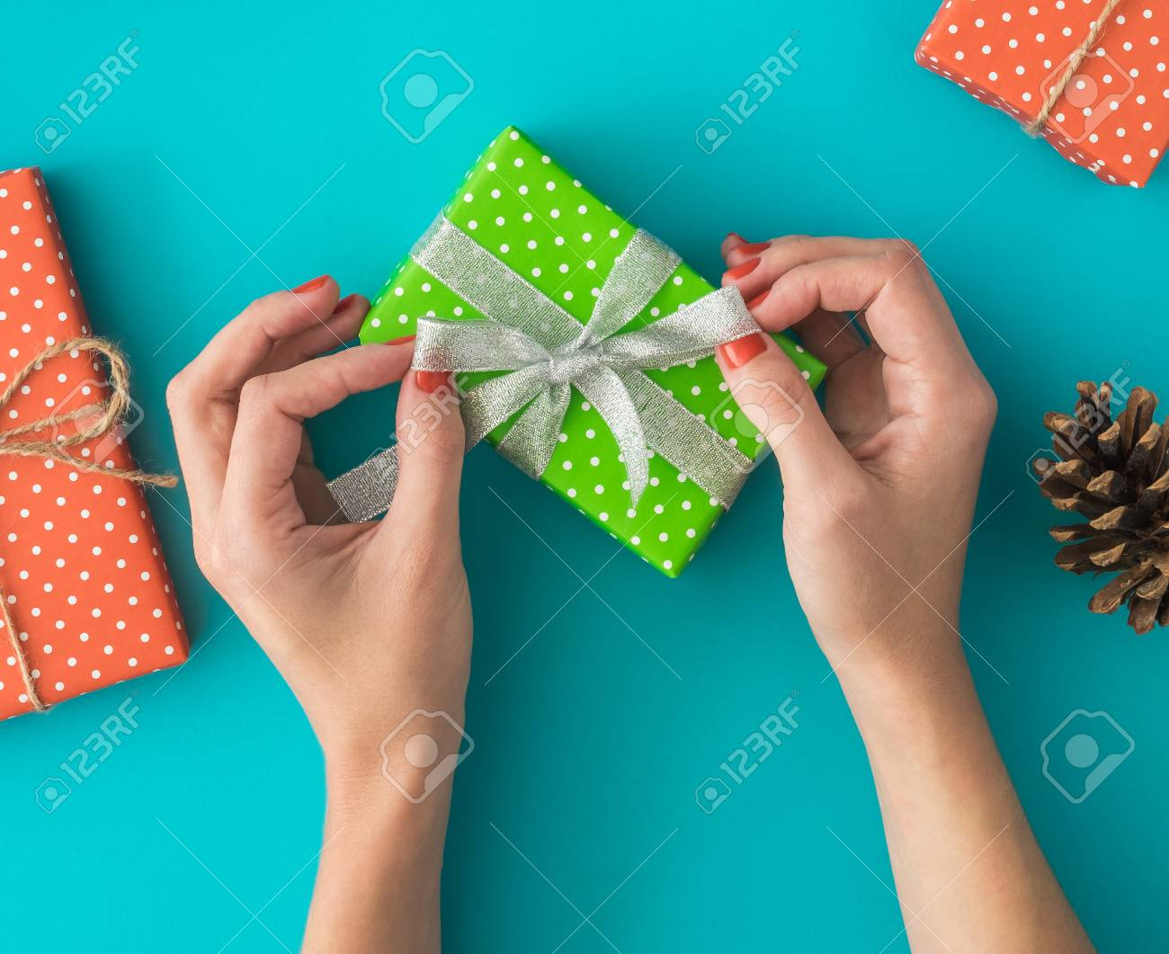 Christmas and New Year holiday composition with gift boxes, pine cone, womens hands pack a gift on the blue background. Top view, flat lay. Copyspace. Stock Photo - 90026707