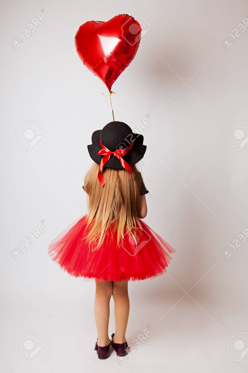 fe258c7c2 little girl in a black red dress and black hat with a red balloon on a