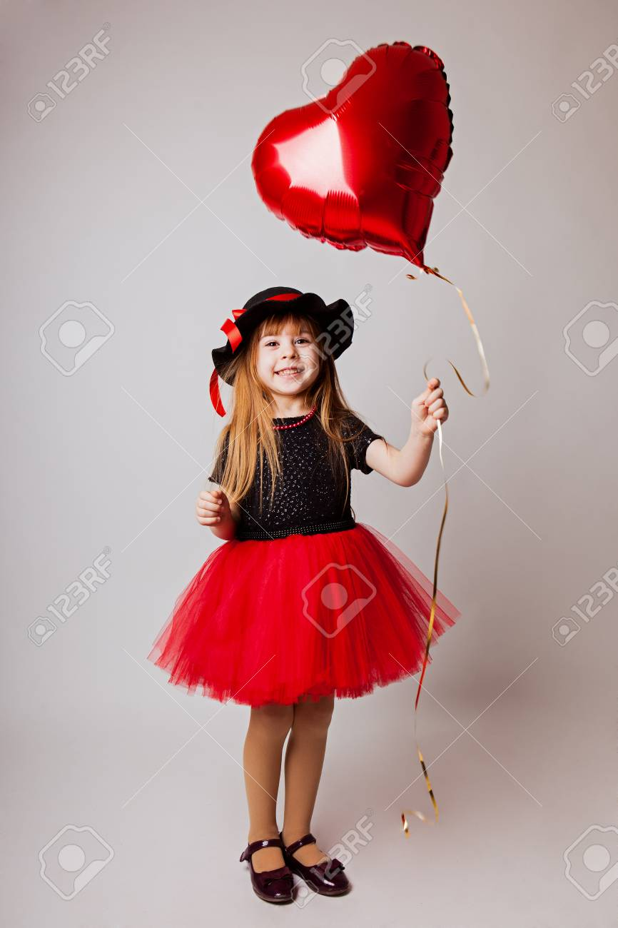 little girl smiling in a black red dress and black hat with a red heart  balloon 1ef7dc0cdb4