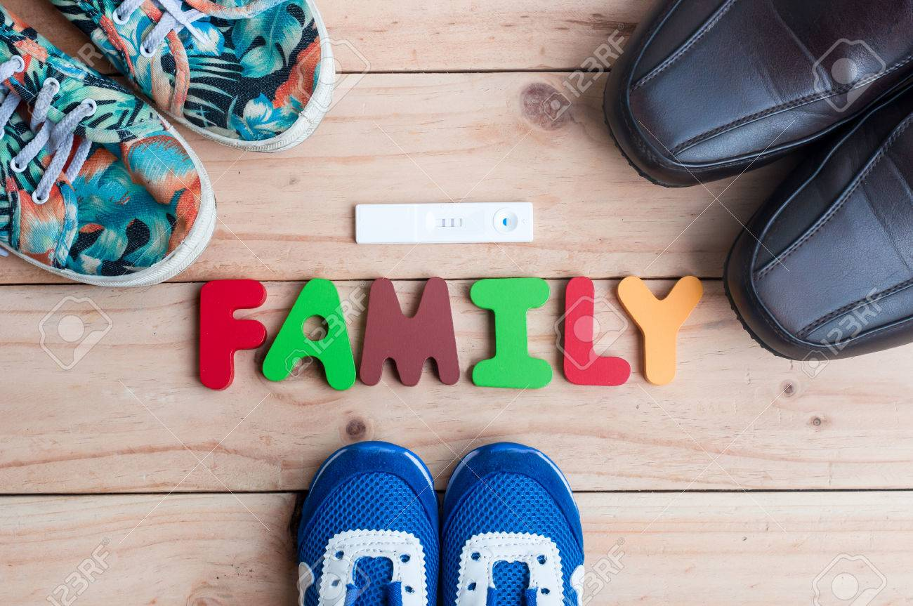 0449956832a0 Shoes for the entire family and new member with family alphabet on the  wooden floor Stock