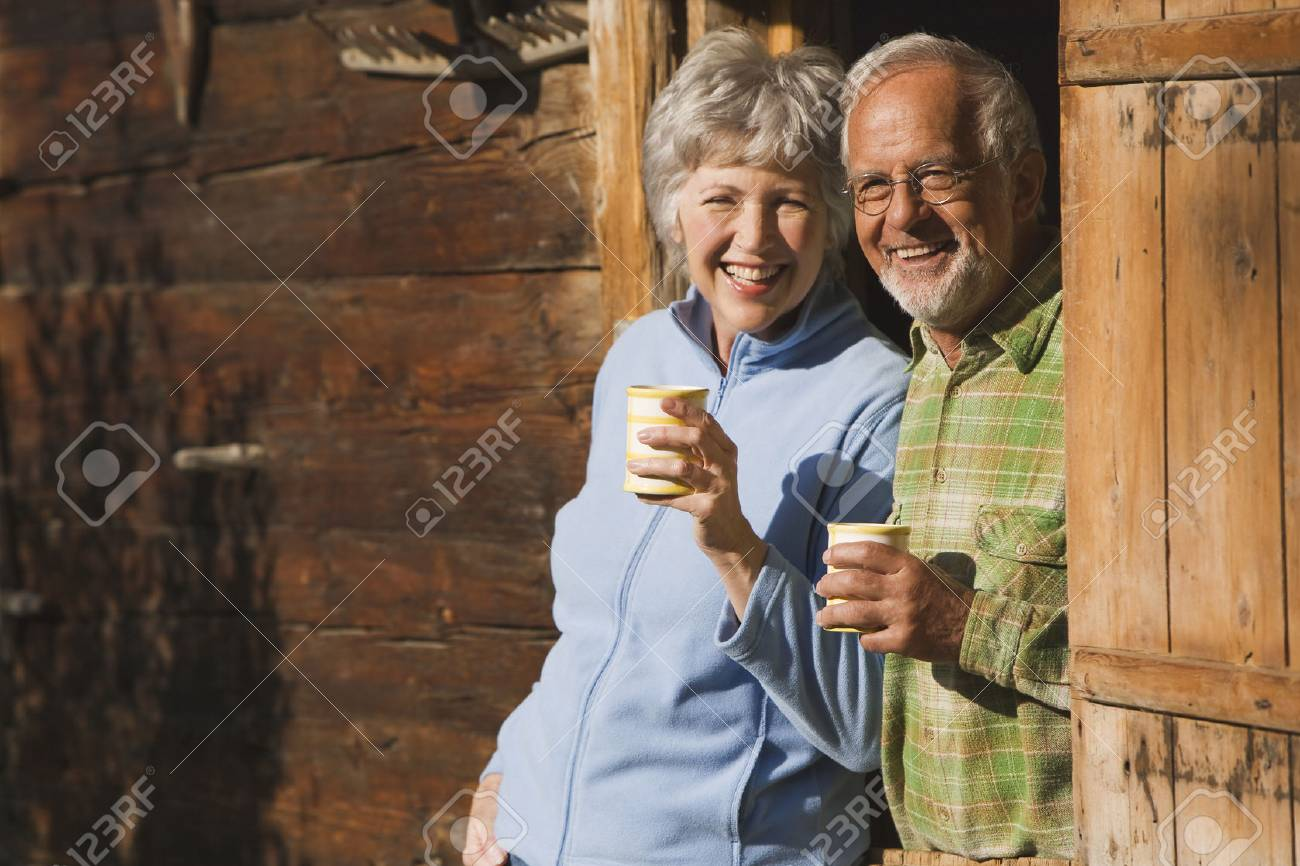 Austria, Karwendel, Senior couple leaning on log cabin's entrance holding mugs - 29823875