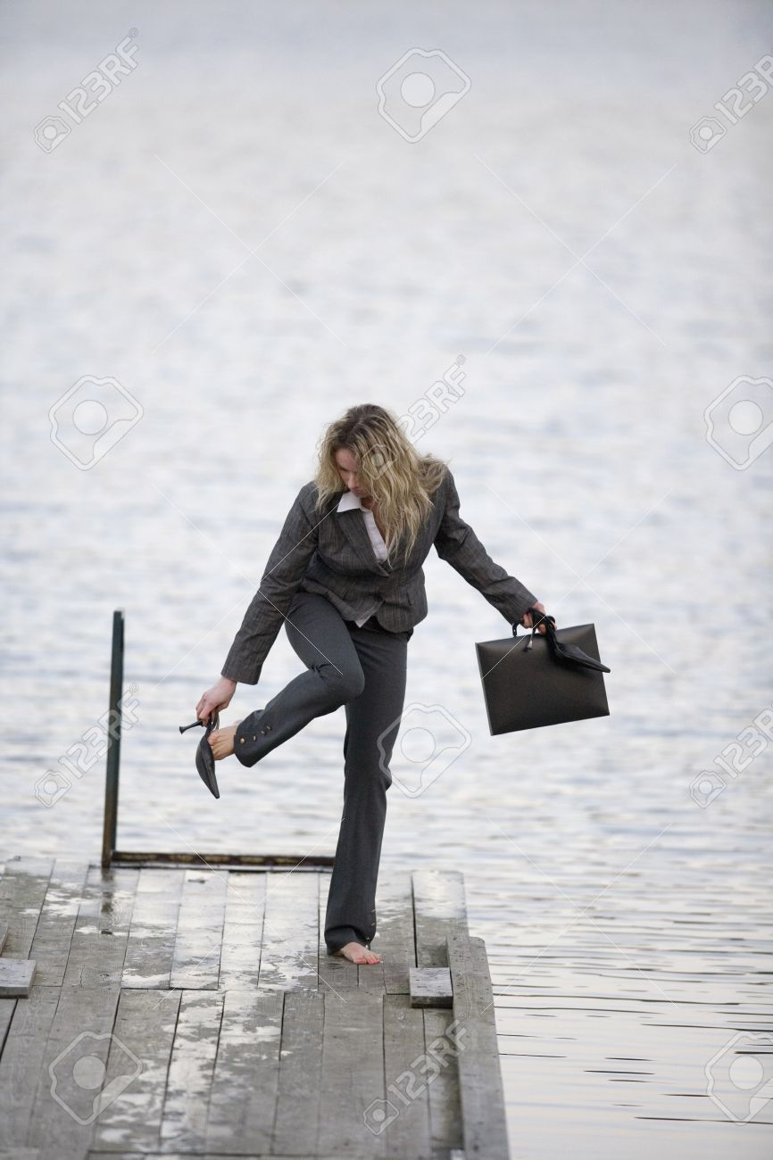 businesswoman standing on jetty, taking off shoes stock photo