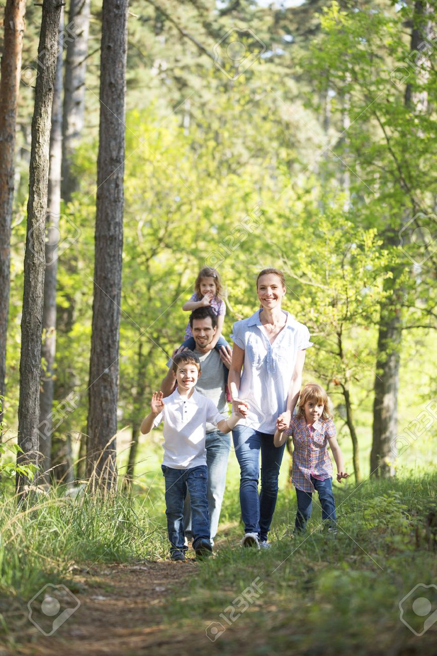 Happy family taking a walk in forest stock photo 33571881