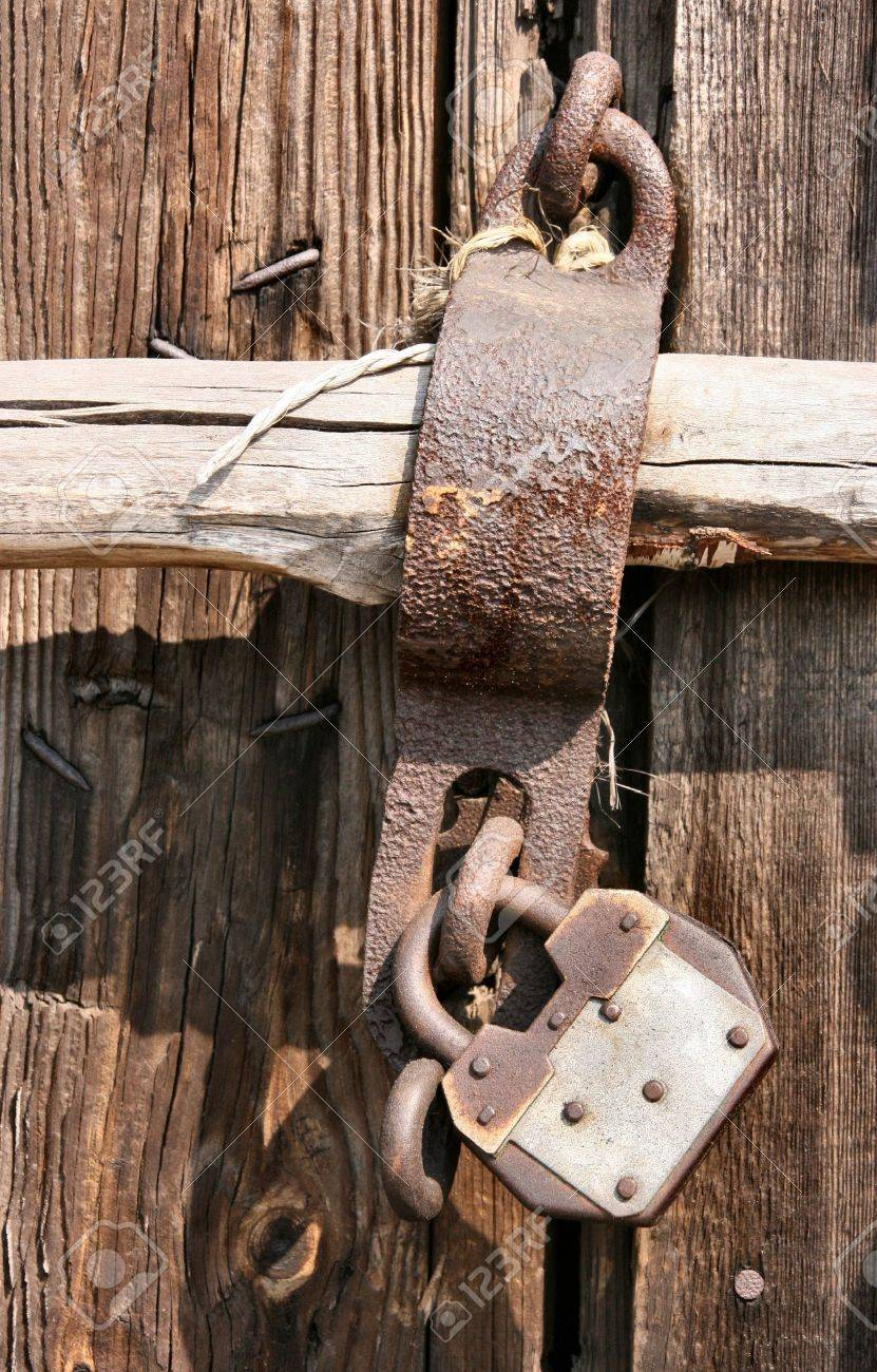 Wooden door to a warehouse and a metal pad lock. Closed and secure. Stock Photo - 943536
