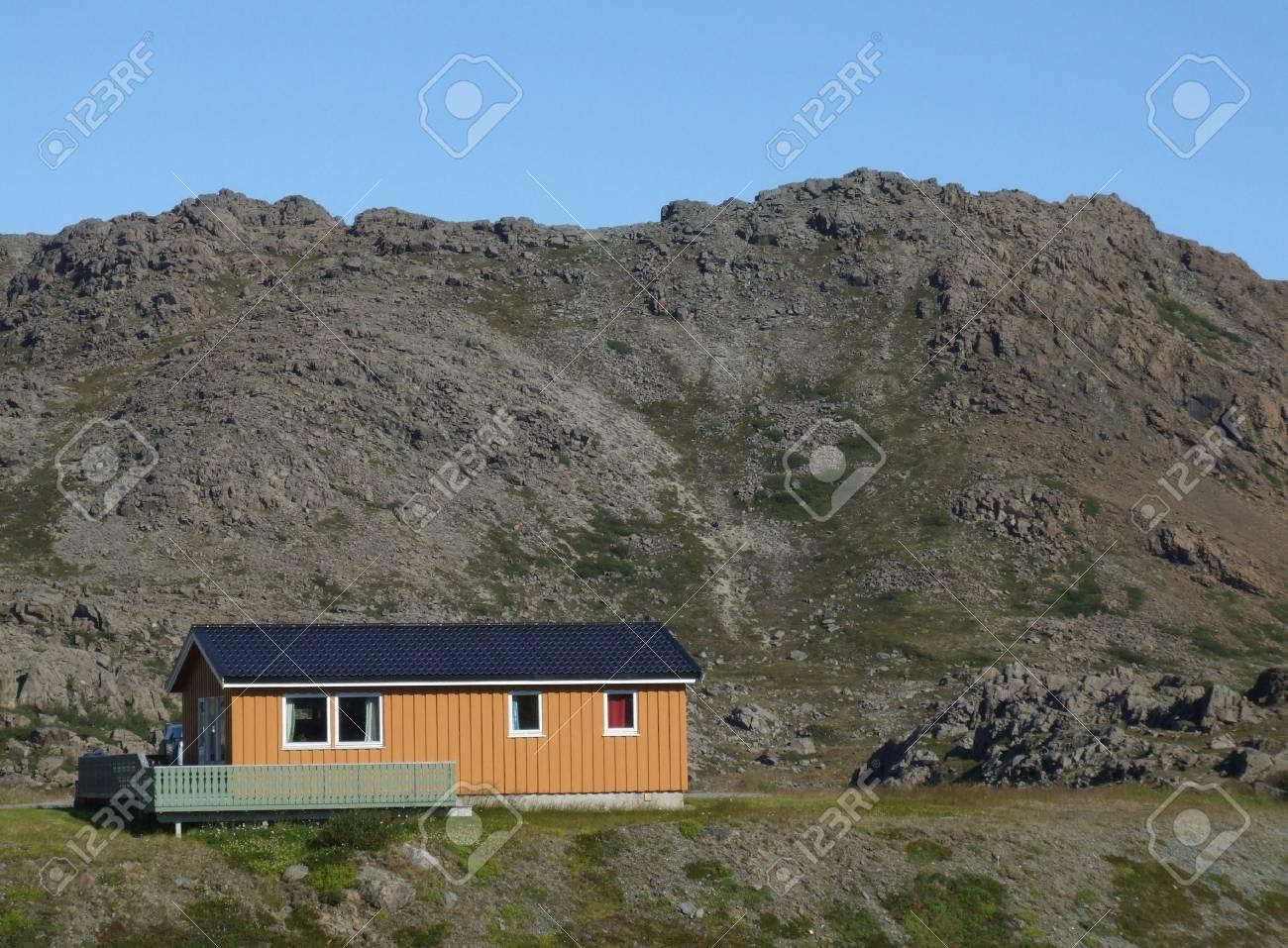 Small orange wooden lodge in Norwegian mountains. Stock Photo - 1052630