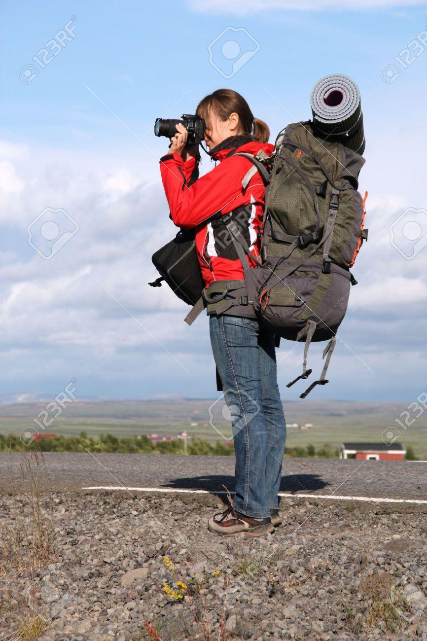 Female tourist taking photos. Girl backpacker, travel photographer in Iceland. Stock Photo - 5337821