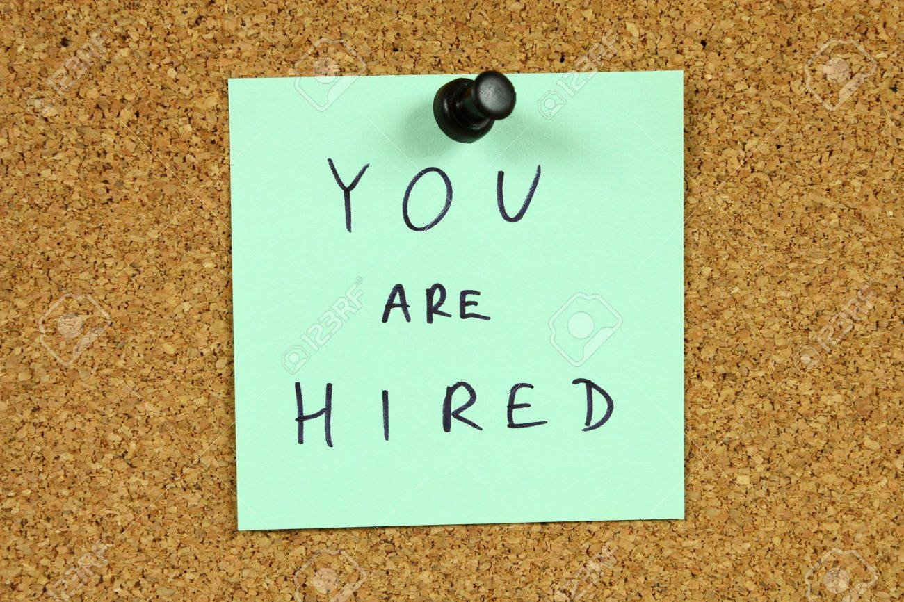 Green small sticky note on an office cork bulletin board. You are hired message. Career success, new employment. Stock Photo - 5917157