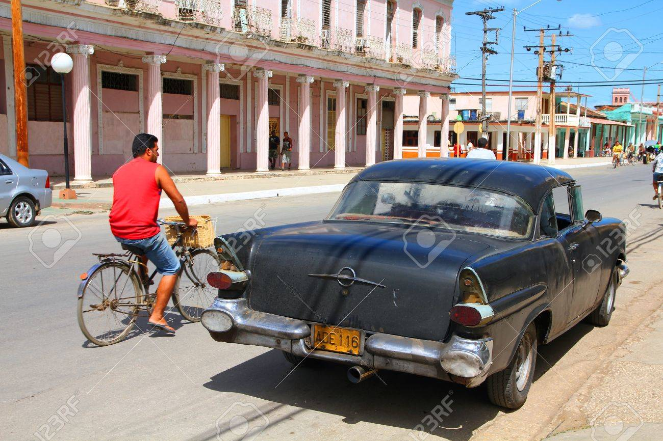 MORON, CUBA - FEBRUARY 19: Cyclist Rides Past Old Car On February ...