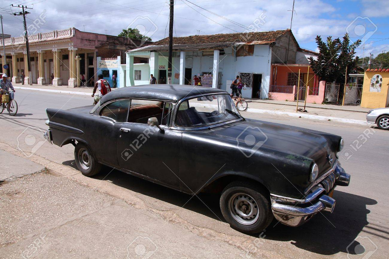 MORON, CUBA - FEBRUARY 19, 2011: People Walk Past Old Car In.. Stock ...