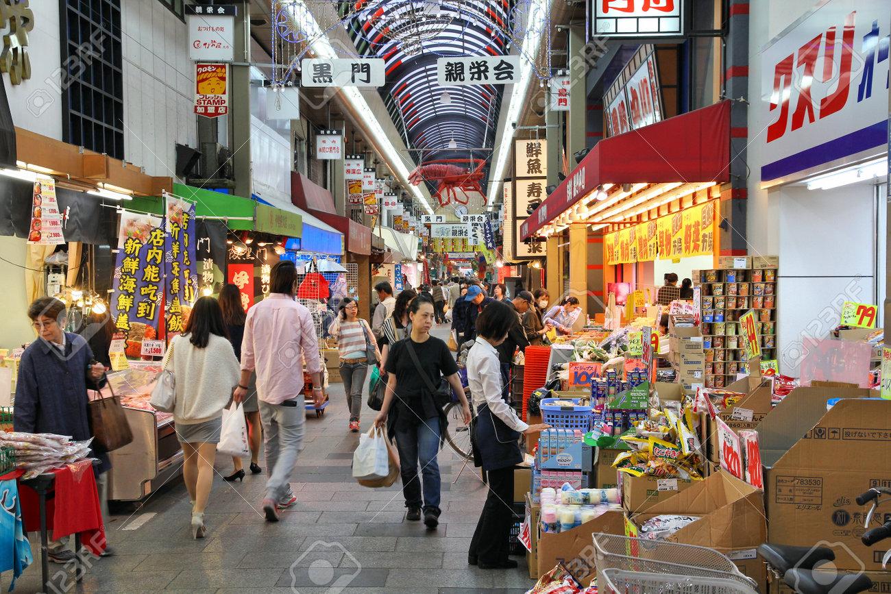OSAKA, JAPAN - APRIL 25, 2012: Shoppers visit Nipponbashi Kuromon market in Osaka, Japan. According to Tripadvisor, it is currently among best 3 shopping places in Osaka. - 64810244