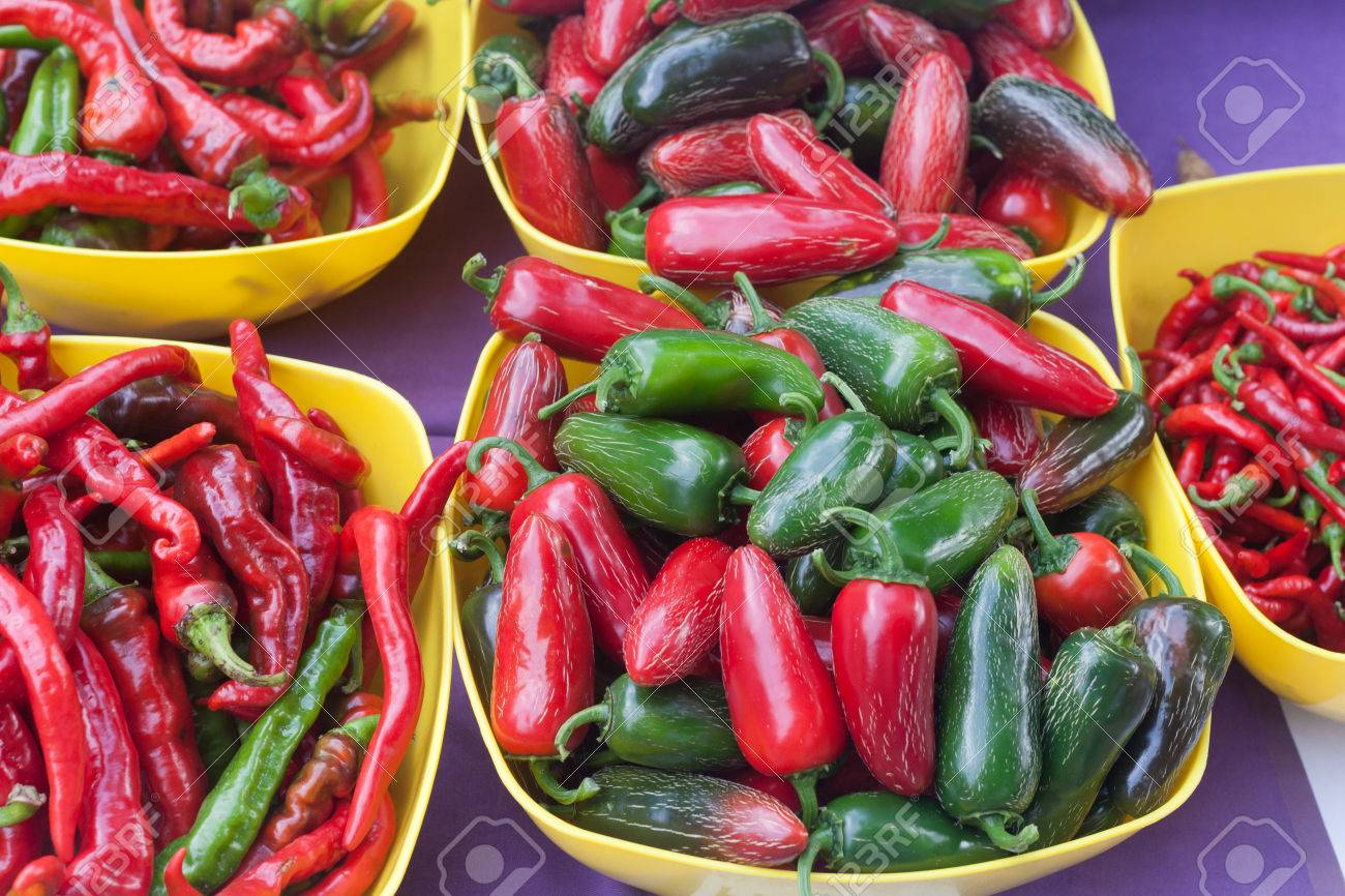 Yellow bowls of red and green spicy pepper varieties