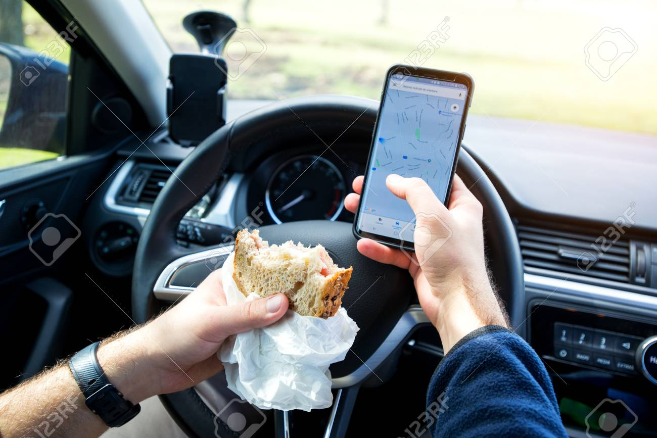 man eating and texting while driving car - 106317982